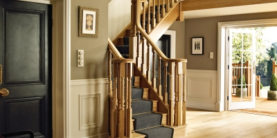 Elegant oak staircase with traditional turned spindles, rising from grand hallway